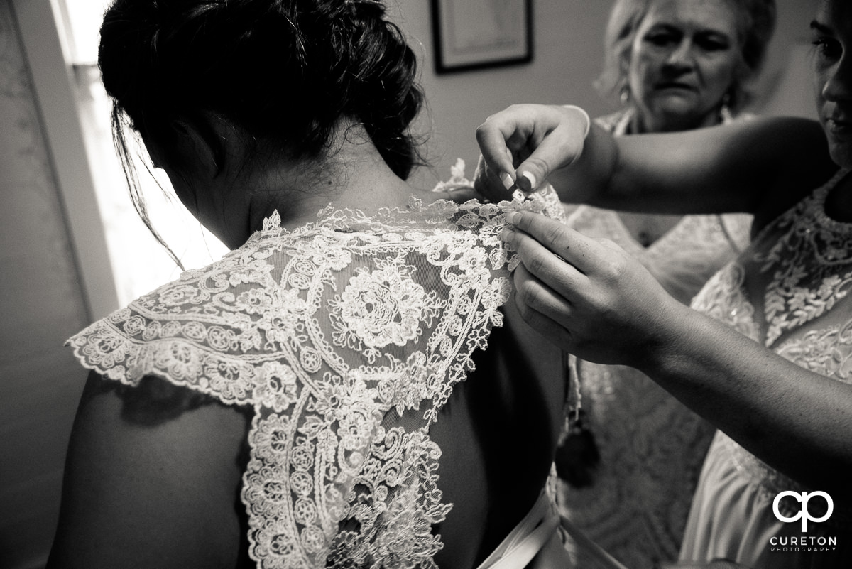 Bride's sisters helping her into her dress.