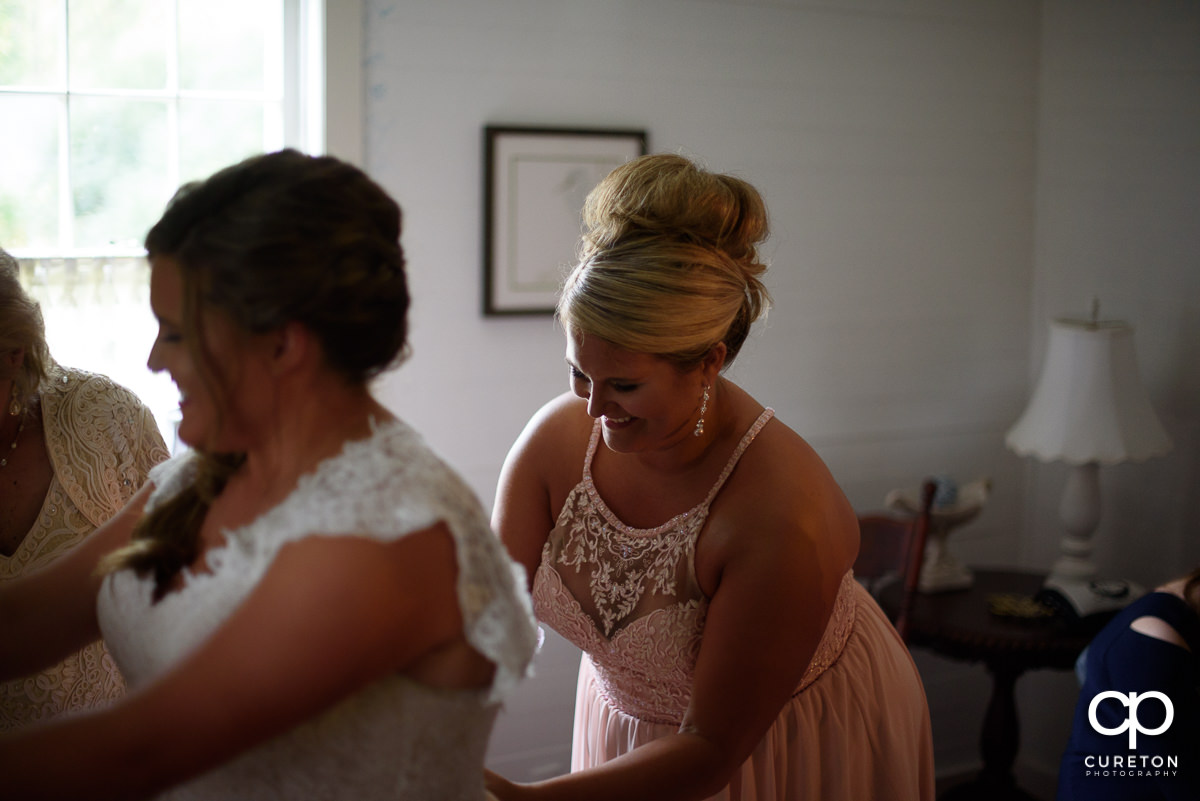 Brides sister zipping the back of her dress.