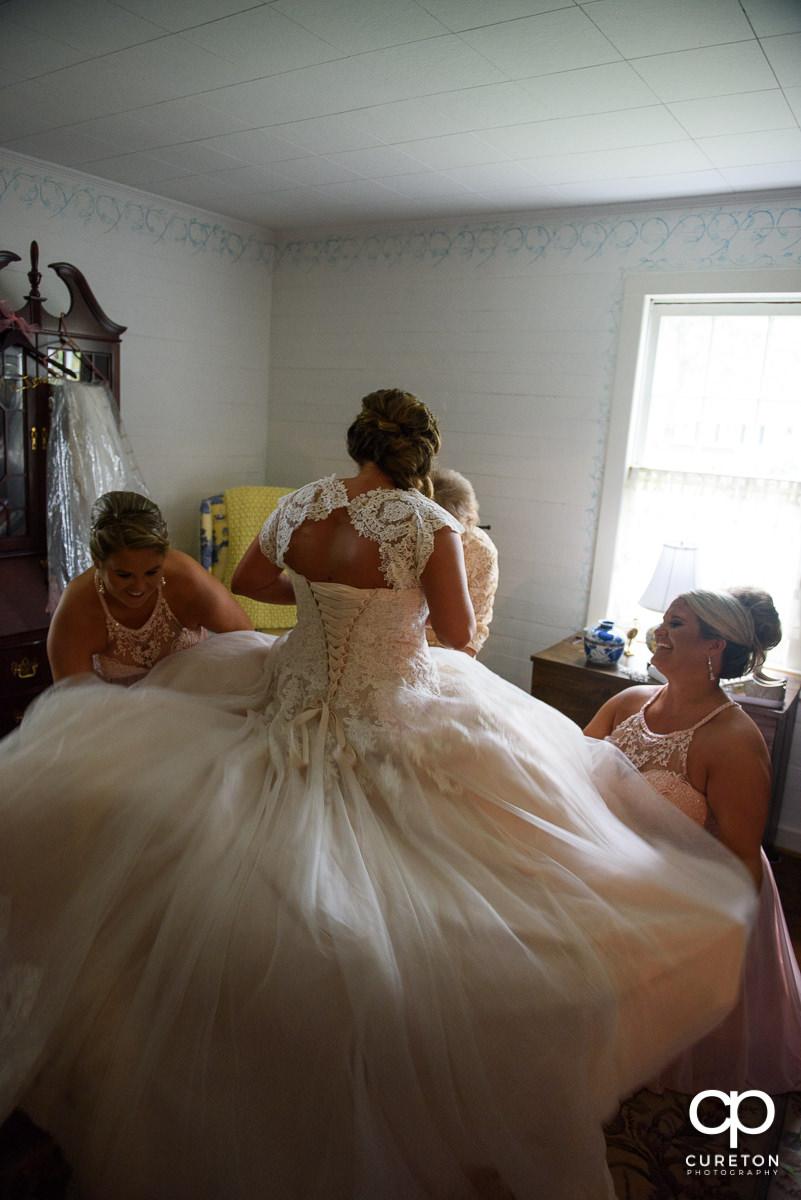 Bridesmaids helping fluff the bride's dress.