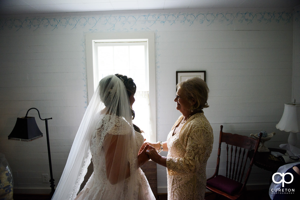 Bride and her mother sharing a moment before the wedding ceremony.