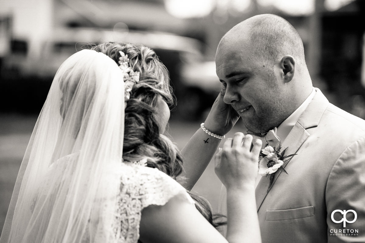 Bride wiping a tear from her groom's eye before the ceremony at The Grove at Pennington.
