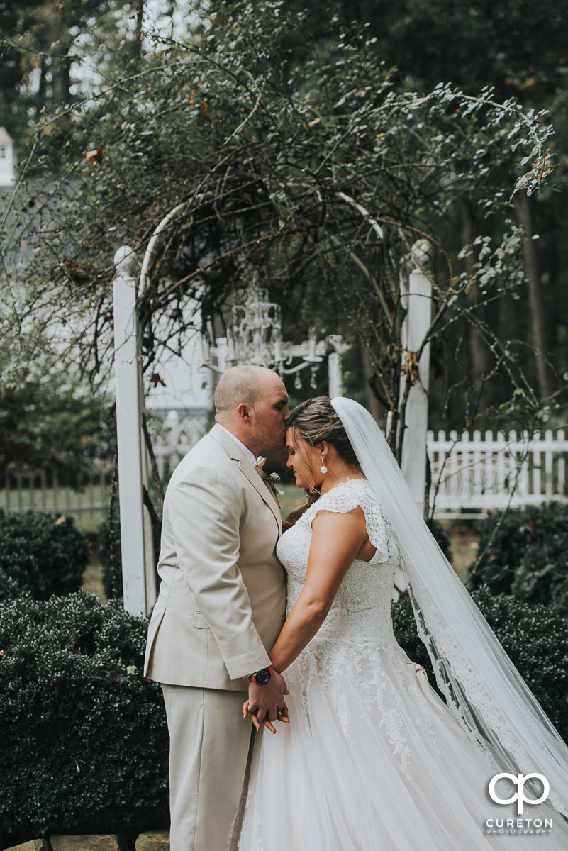 Groom kissing his bride on the forehead before the Grove at Pennington wedding.