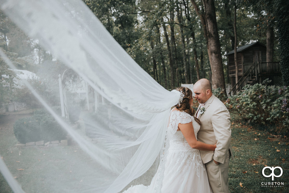 Bride and groom dancing with her cathedral veil blowing in the wind.