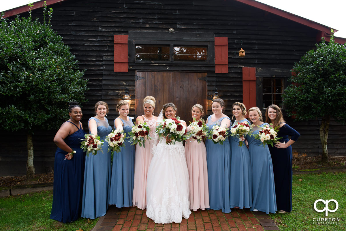 Bride and bridesmaids in from of the Grove at Pennington.