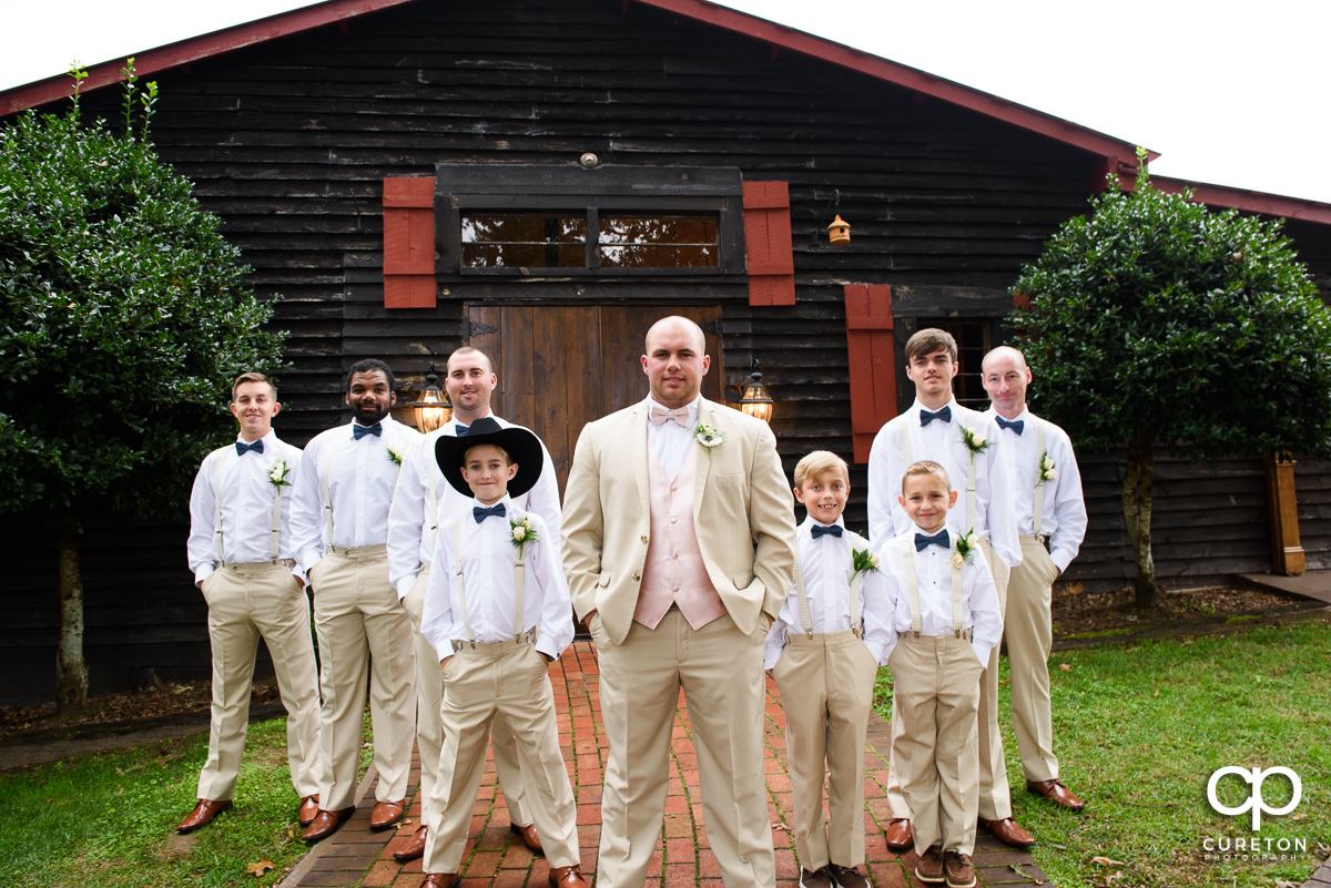 Groom and the groomsmen in front of the barn.