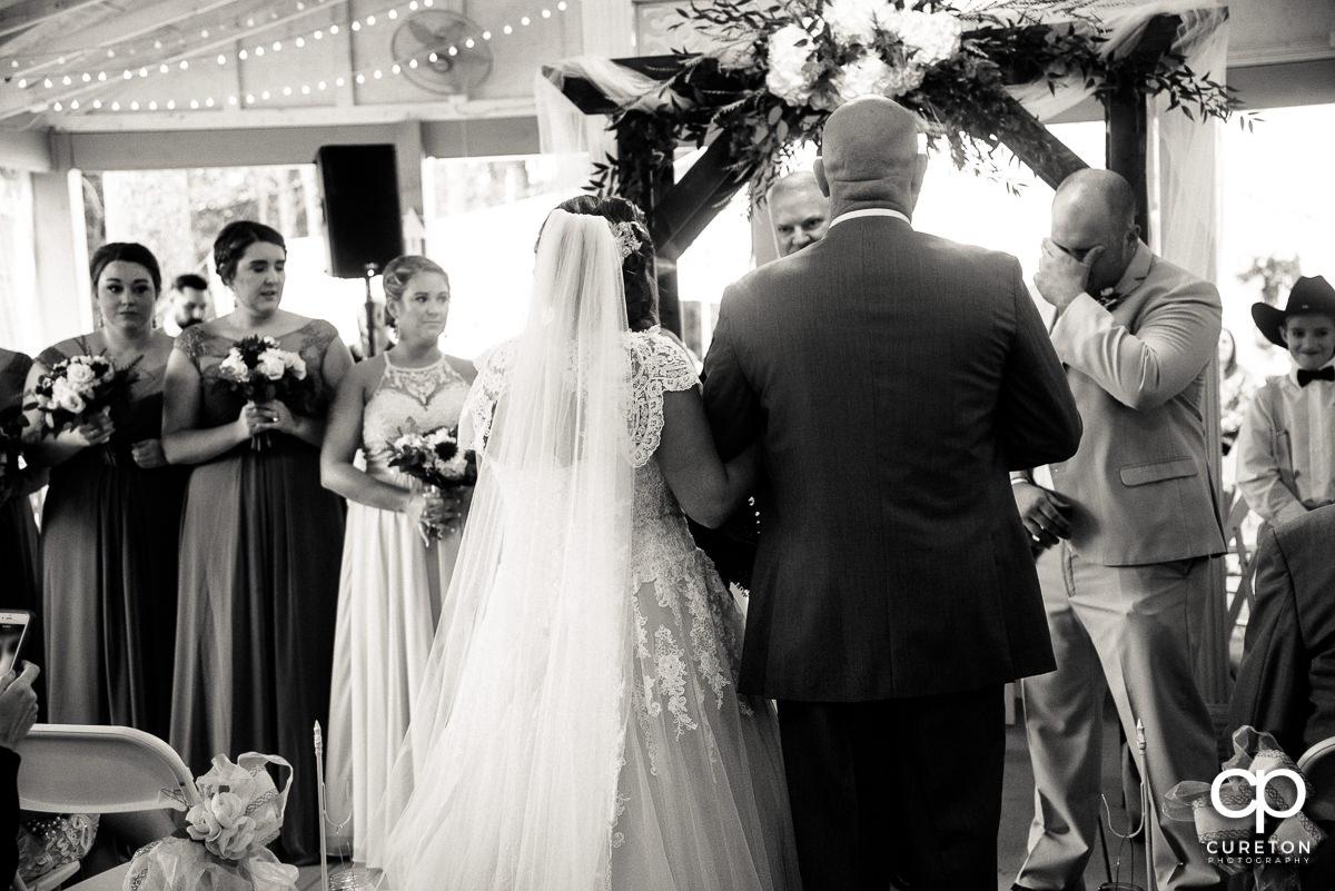 Groom tearing up as a bride walks down the aisle.