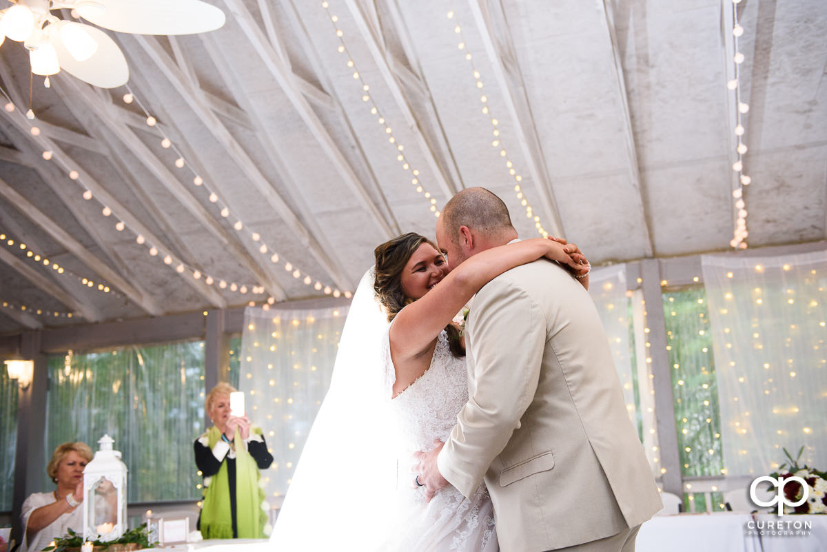 Bride laughing with her groom during their first dance.