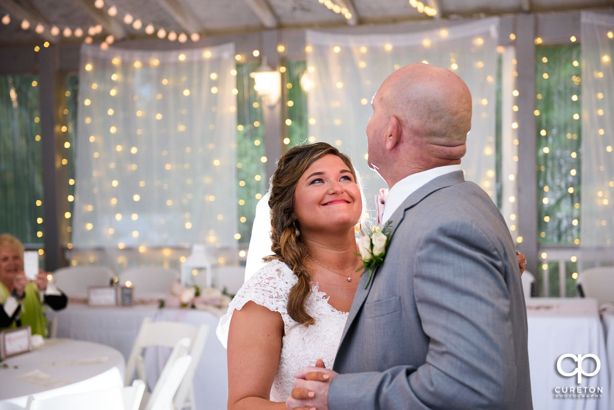 Bride smiling at her father during their first dance.