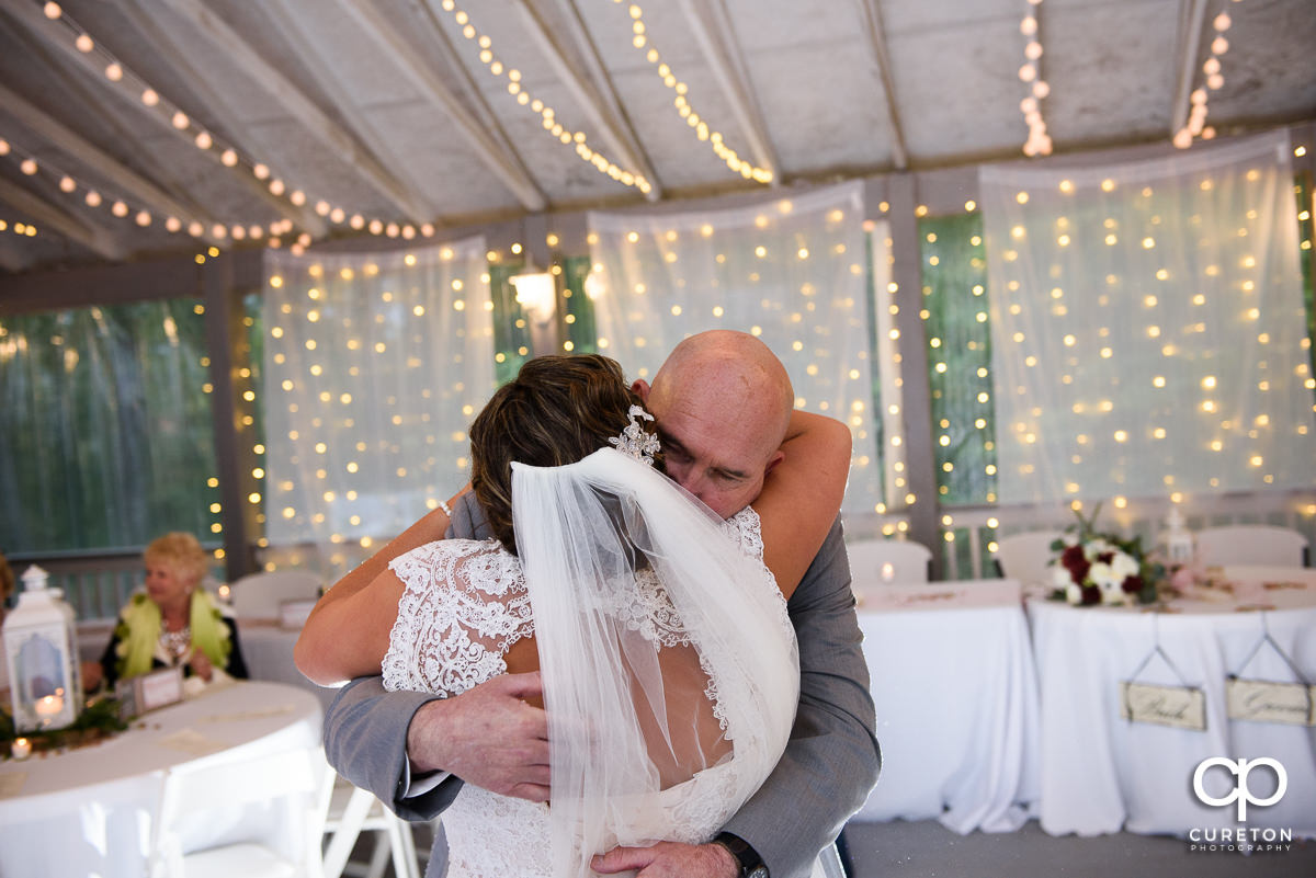 Father of the bride hugging his daughter after they danced at the wedding reception.