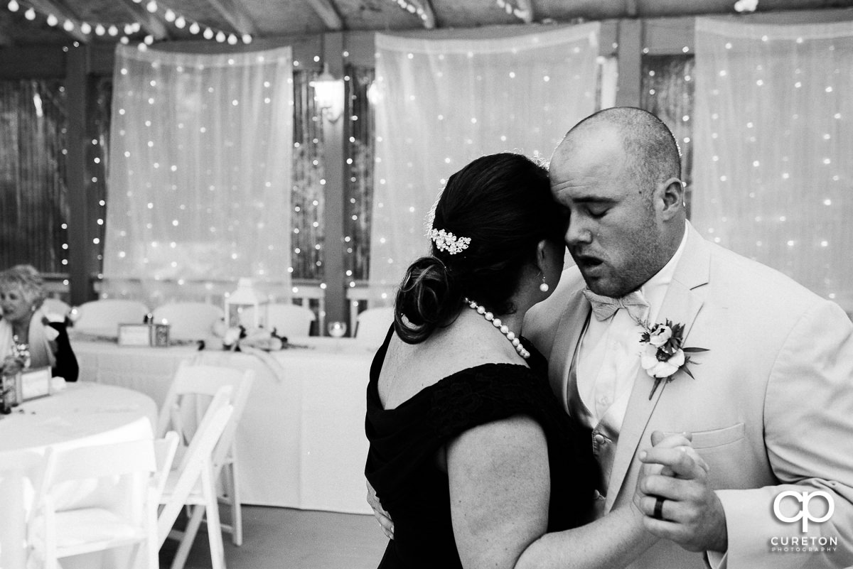 Emotional groom dancing with his mother at the reception.