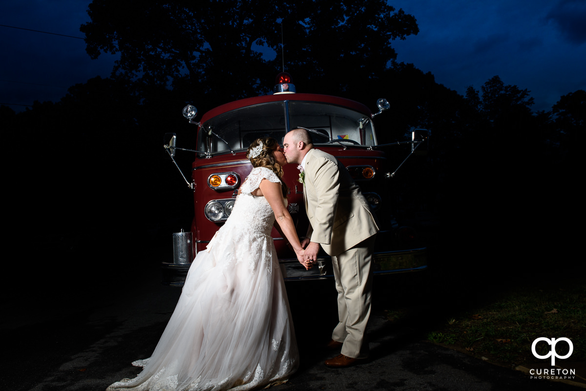 Bride and groom kissing in front of a fire truck.