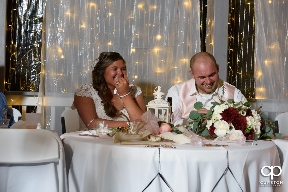 Bride and groom laughing at the toasts.