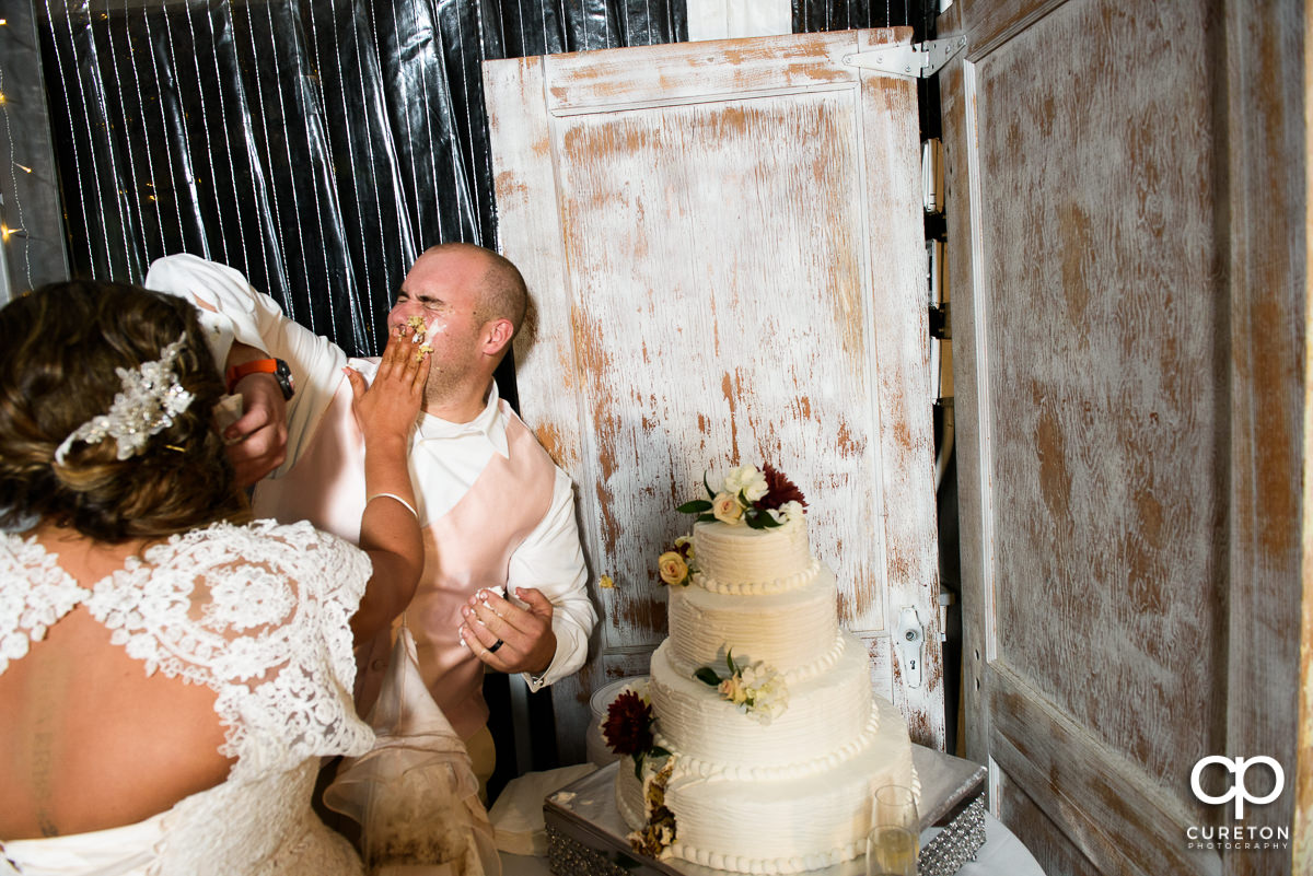 Bride smearing cake on the groom's face.