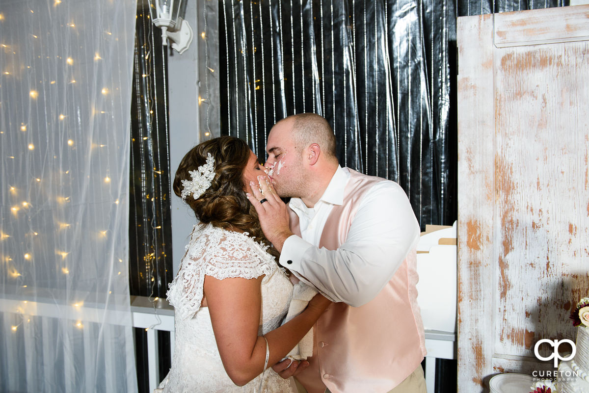 Bride and groom kissing after the cake cutting.