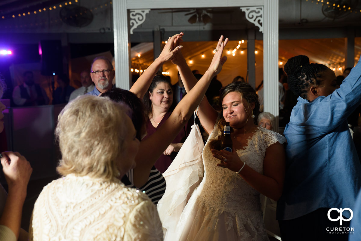 Wedding guests dancing with the bride at the reception.