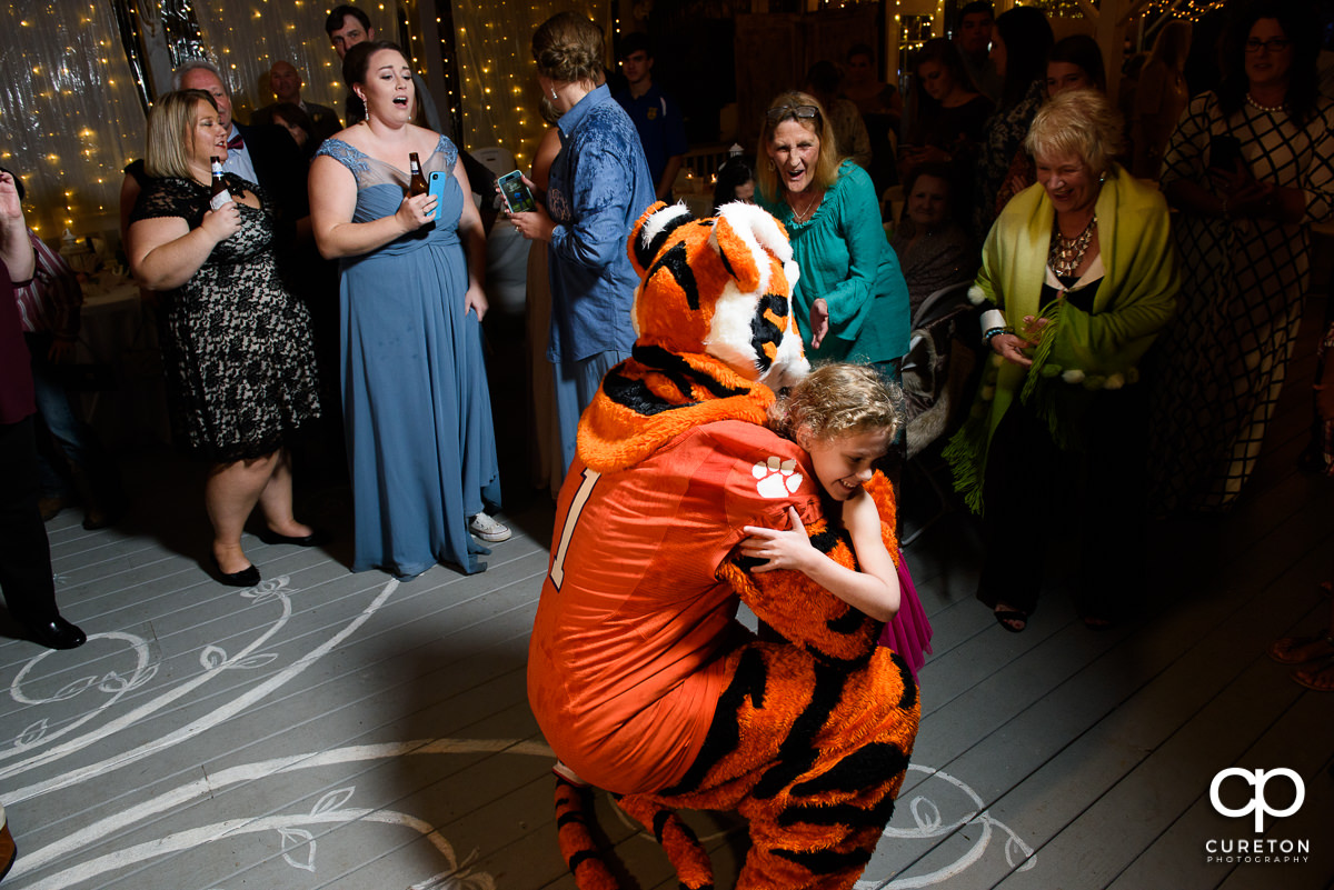 Clemson Tiger hugging a child at the wedding reception at The Grove at Pennington.