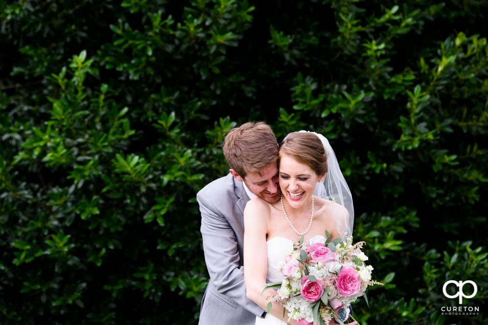 Bride and groom snuggling outside after their wedding at Holly Tree Country Club in Simpsonville,SC.