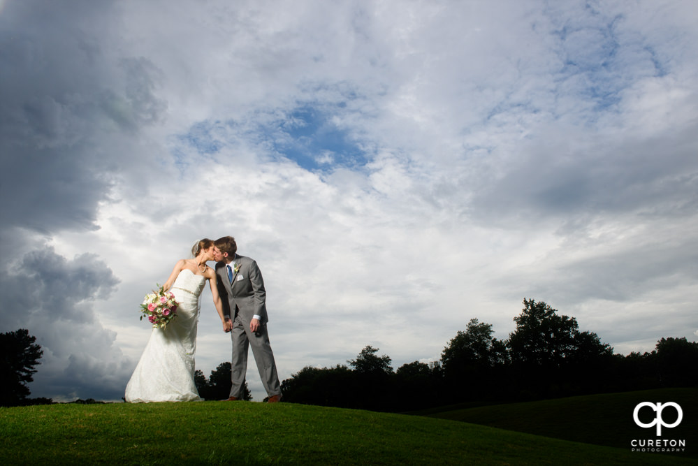Bride and groom kissing on the golf course at Holly Tree Country Club.