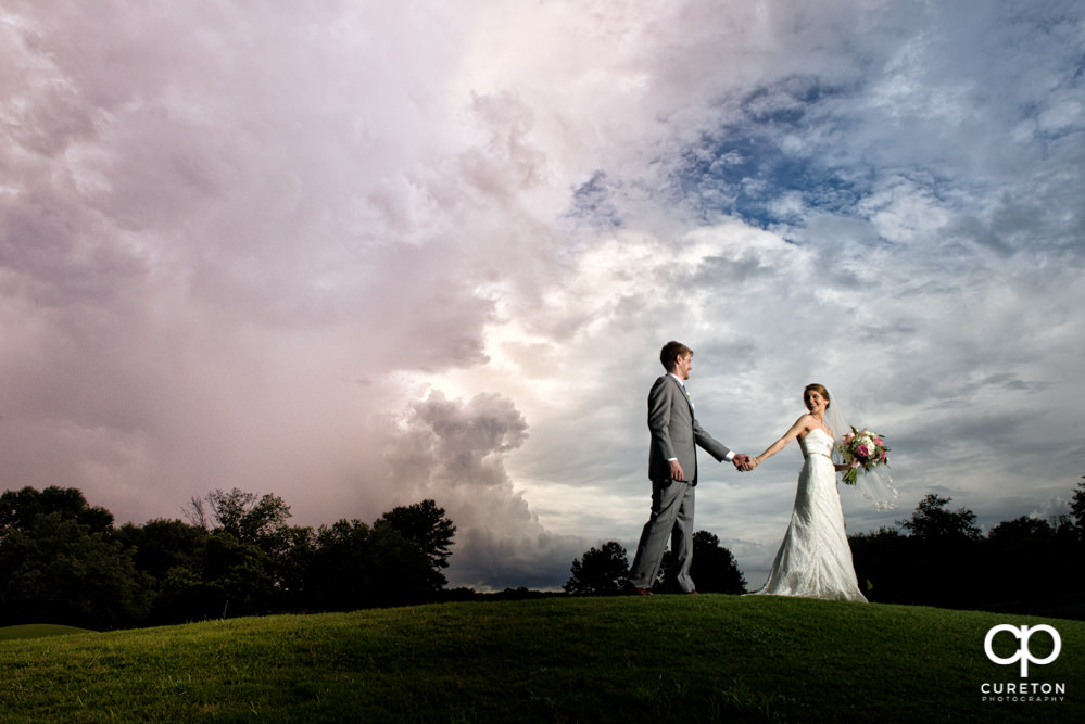 Bride and groom with an amazing sky after their Holly Tree Country Club wedding.