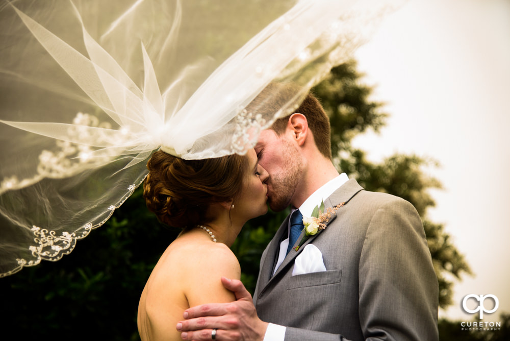 Bride and Groom kissing with her veil blowing in the wind at their Holly Tree Country Club wedding in Simpsonville SC.