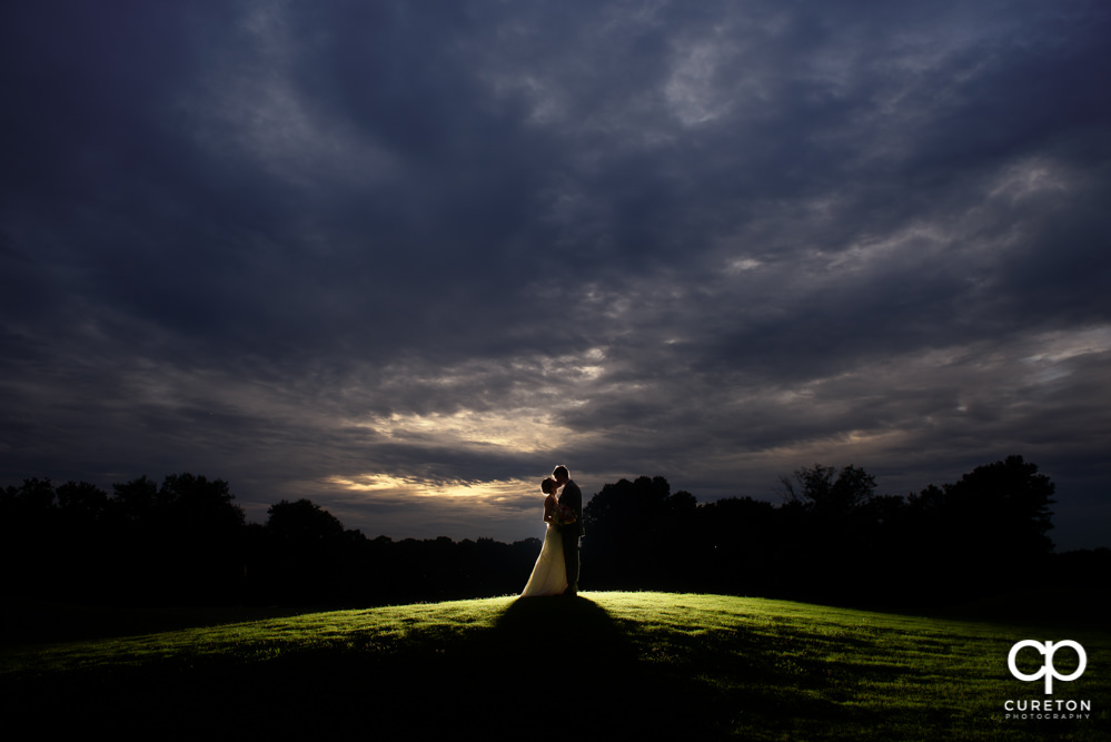 Bride and groom backlit silhouette at sunset after their golf course wedding.