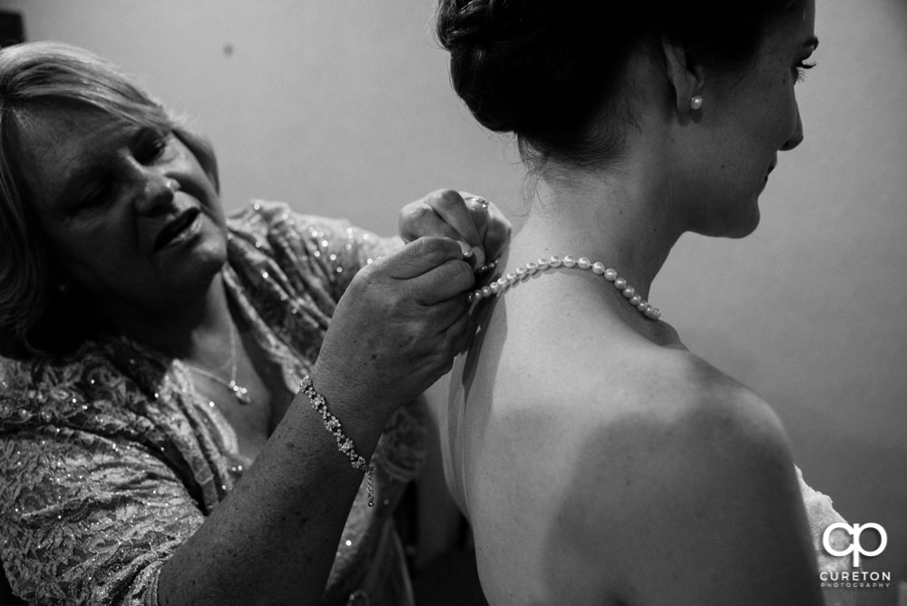 Bride's mom helping bride with jewelry.