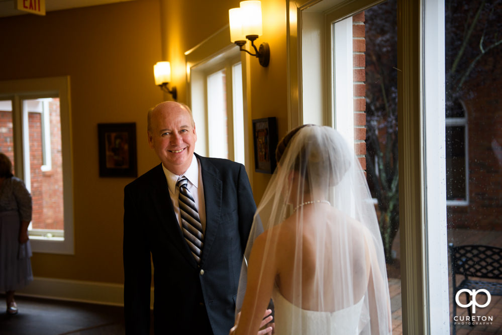 Dad sees his daughter during a first look before the wedding.
