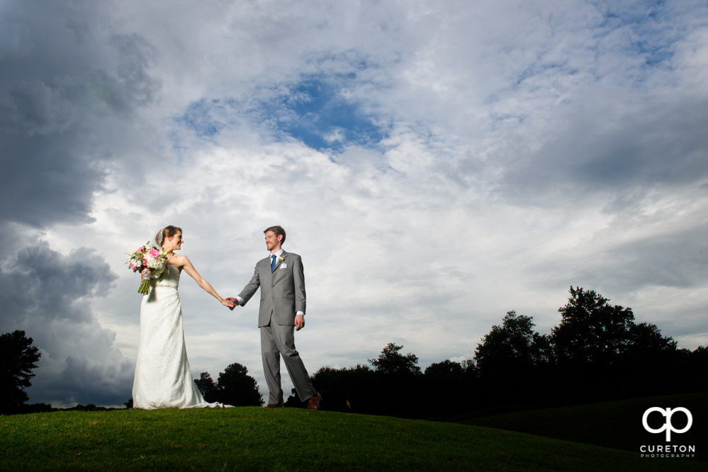 Bride and groom walking on Holly Tree golf course after the wedding.