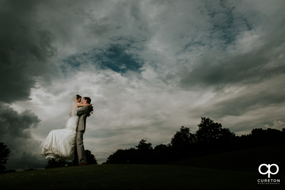 Groom lifting his bride on the golf course at Holly Tree.