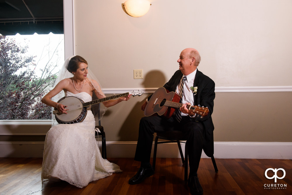 Bride and her father playing guitar and banjo at her wedding reception.