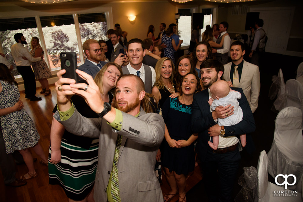 Guests taking a selfie at the wedding reception.