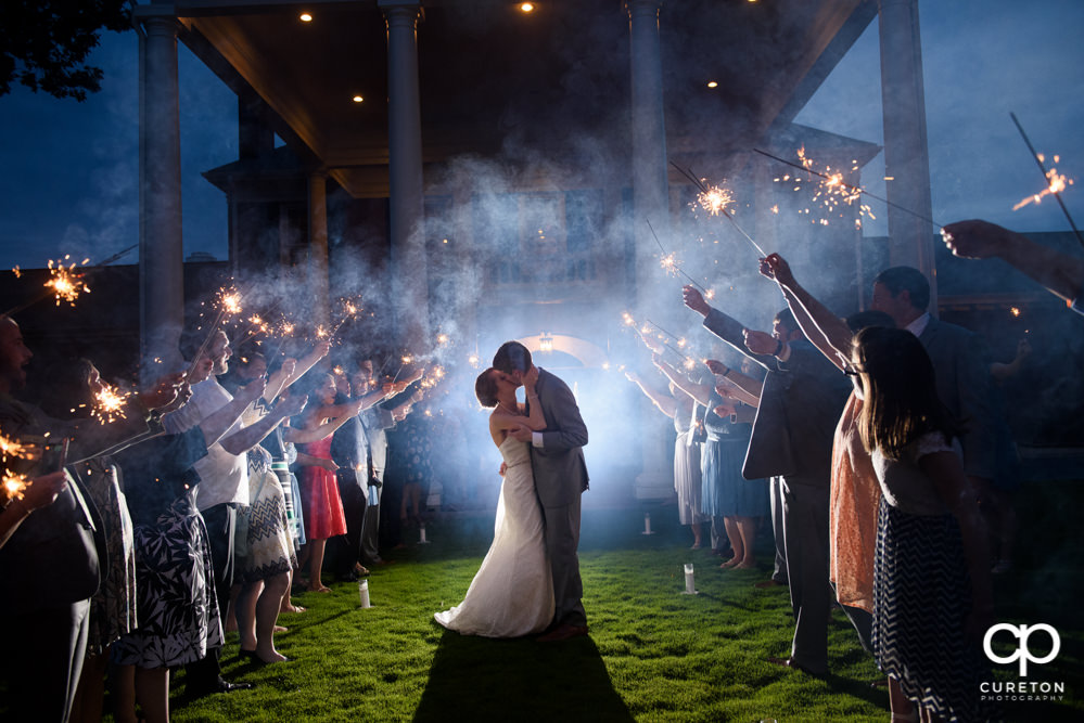 Bride and groom making a grand exit though sparklers after their Holly Tree wedding reception.