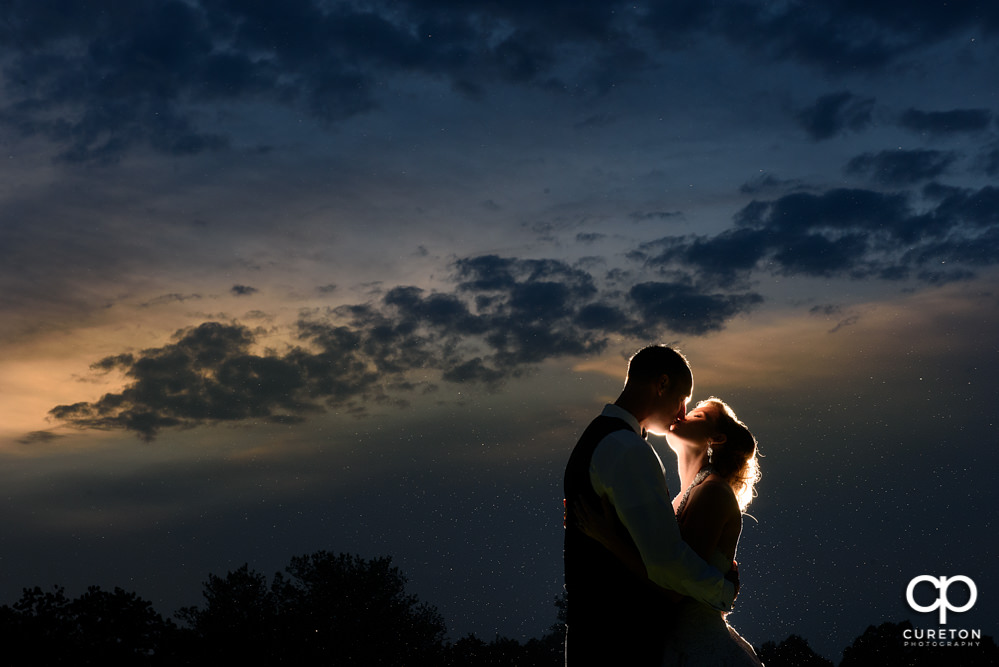 Bride and groom kissing in the sunset.