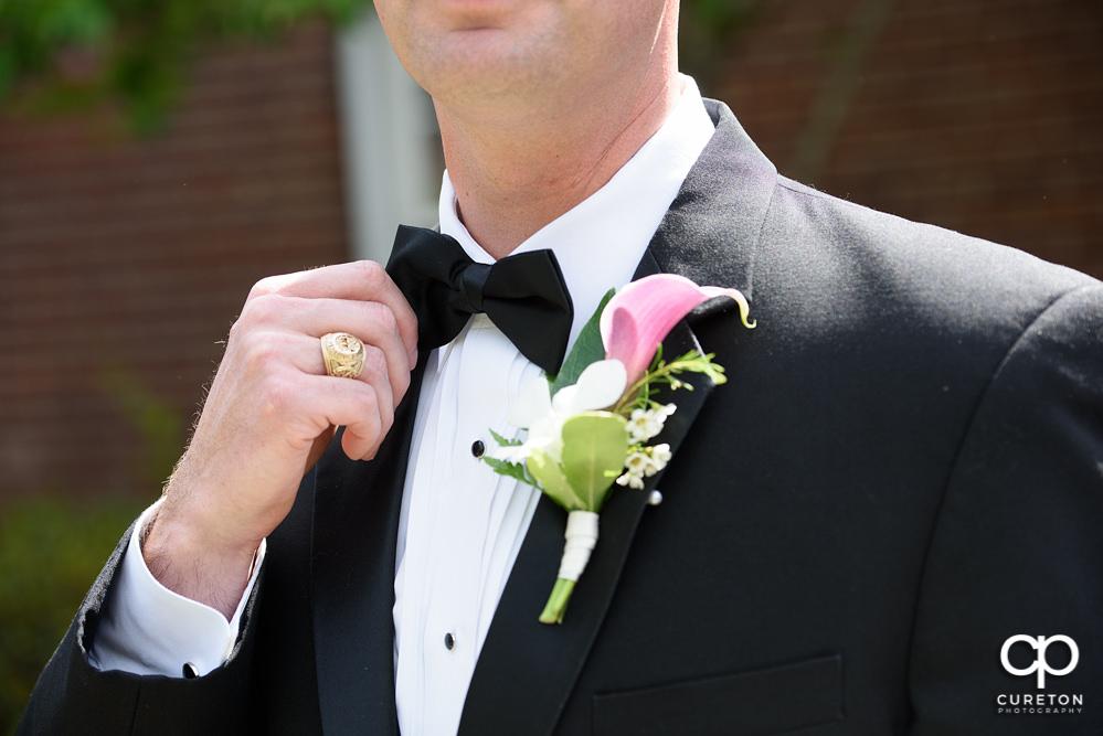 Groom holding his tie.