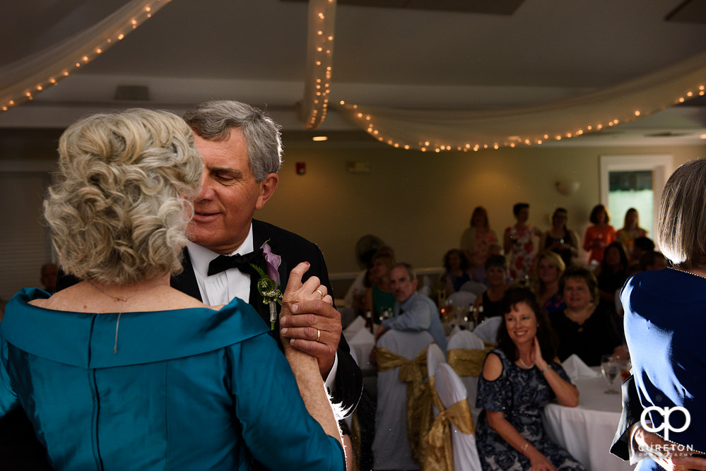 Bride and groom having a first dance at the wedding reception at Holly Tree Country Club.