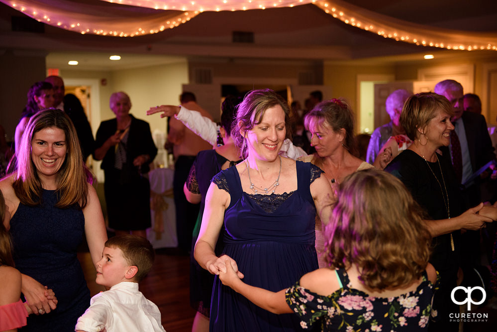 Wedding guests dancing at a Holly Tree Country Club wedding reception while Uptown Entertainment dj's.