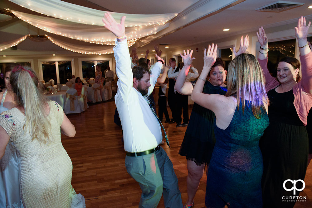Wedding guests dancing at a Holly Tree Country Club wedding reception .