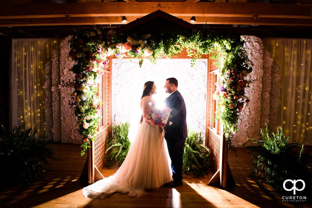 Bride and groom underneath a custom built arbor during their Huguenot Loft wedding in Greenville,SC.