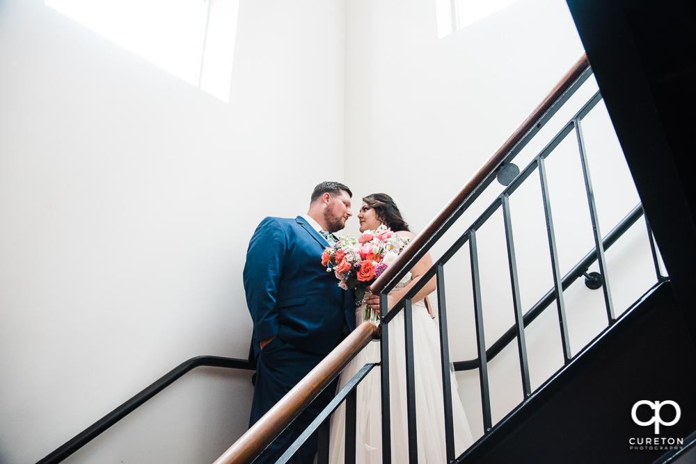 Bride and Groom on the stairs after their Huguenot Loft wedding in Greenville,SC.
