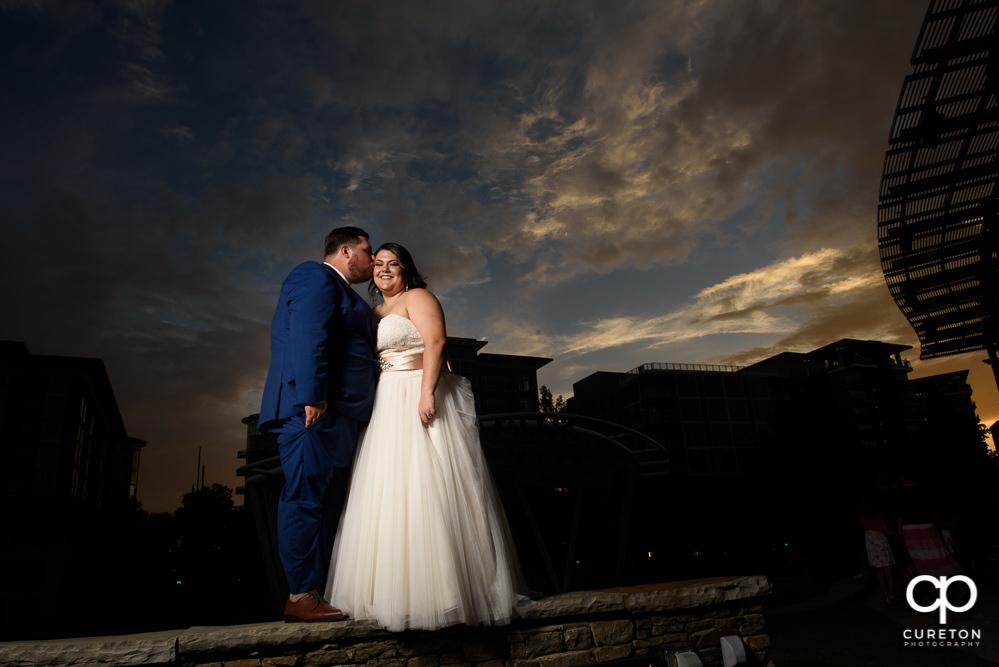 Groom kissing his bride after their Huguenot Loft wedding in Greenville,SC.