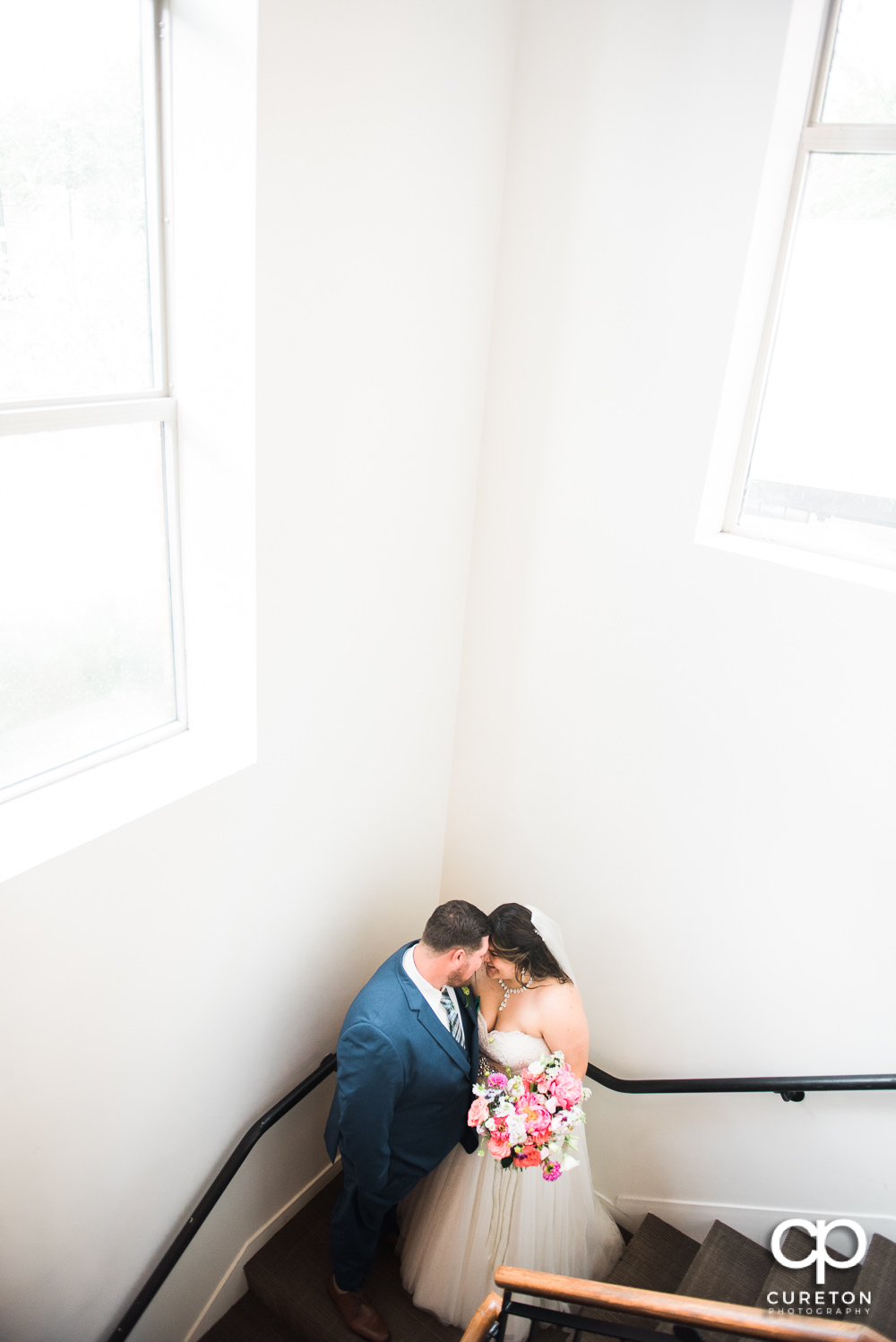 Bride and groom on stairs after their Huguenot Loft wedding in Greenville,SC.