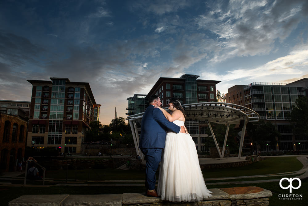 Bride and groom dancing at sunset with the backdrop of downtown Greenville.