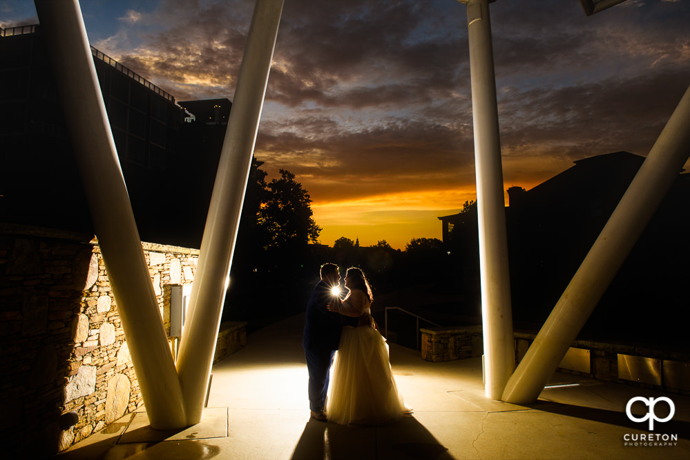 Bride and groom on a stage behind the Huguenot Loft at sunset.