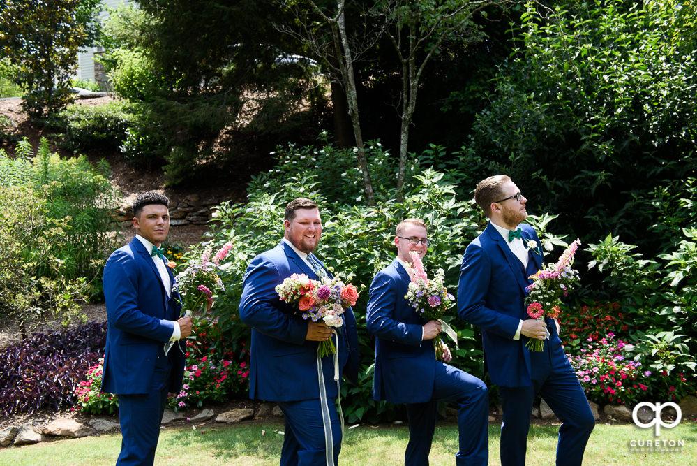 The groomsmen holding flowers.