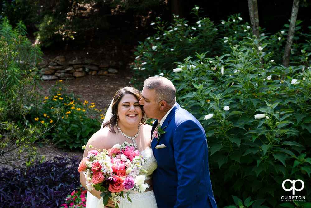 Bride's dad kissing her on the cheek.
