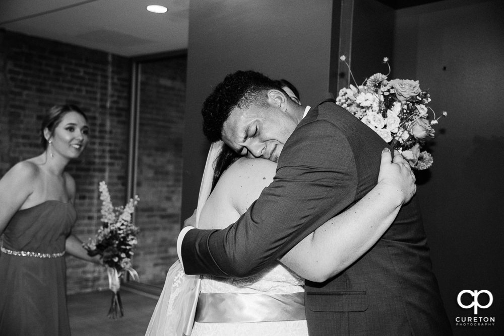 Bride's brother hugging his sister.