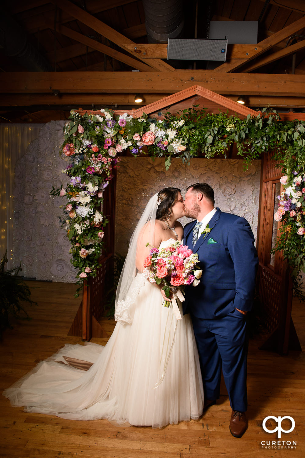 Bride and groom kissing under the arbor at their Huguenot Loft wedding.