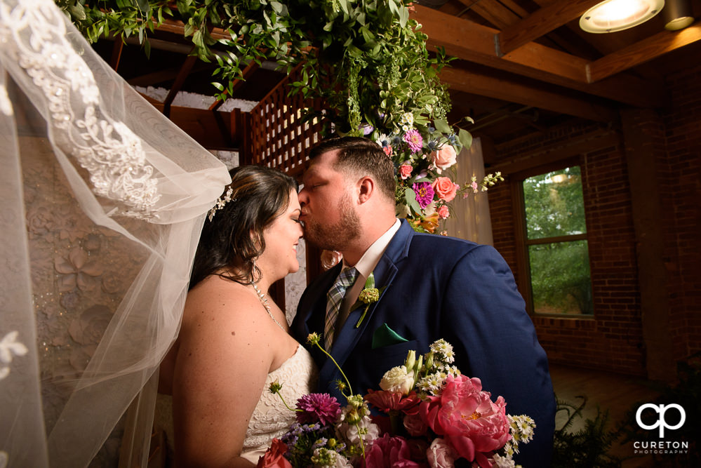 Groom kissing his bride on the forehead at their Huguenot Loft wedding.