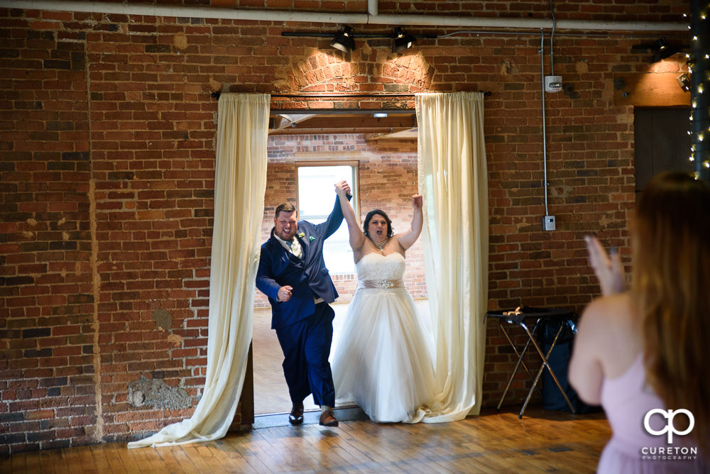 Bride and groom making an entrance into the reception.