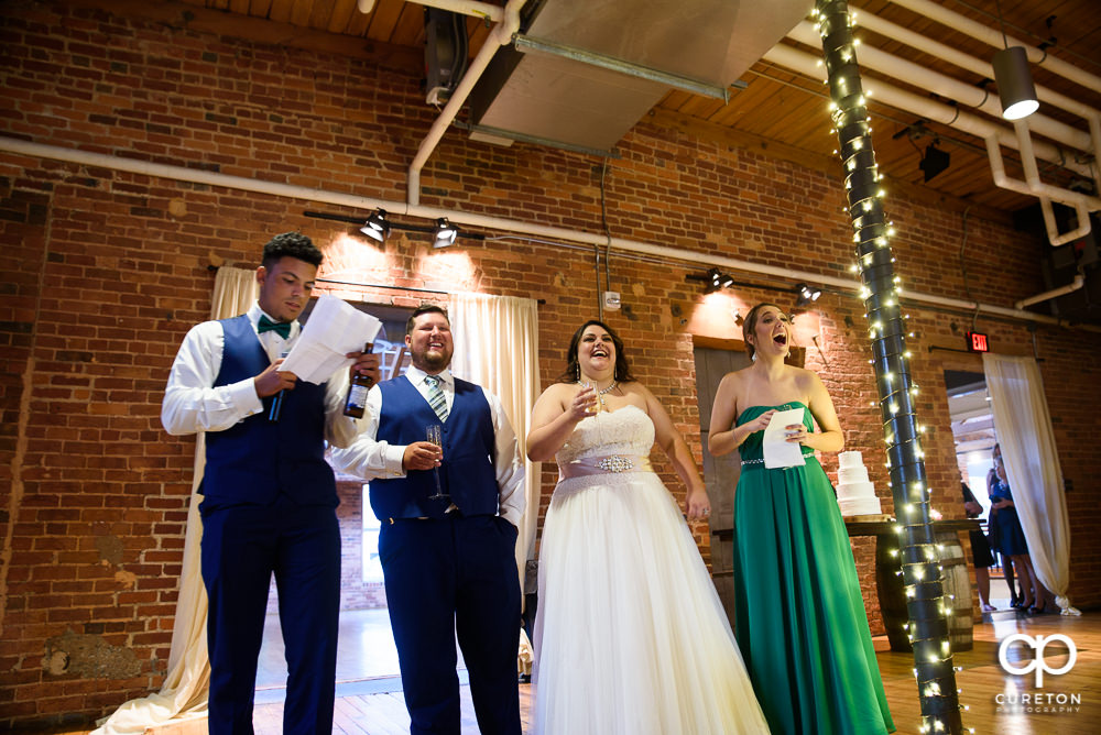 Bride and groom look on as the best man and maid of honor give toasts.